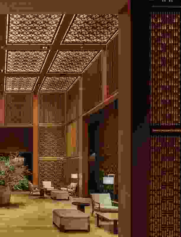 Amanyangyun's hotel lobby is a soaring cubic volume within a free- standing box of lattice. The lattice screens are made from nanmu timber, used historically in aristocratic Chinese buildings and revered for its silken surface, gold fleck and fragrance.