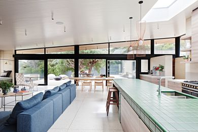 A green-tiled bench references foliage and defines the kitchen within the open-plan space.