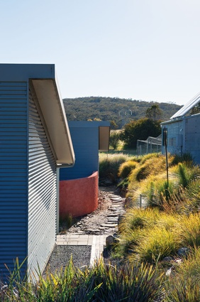 A dry garden of stones and grasses sits between the house and the slope.