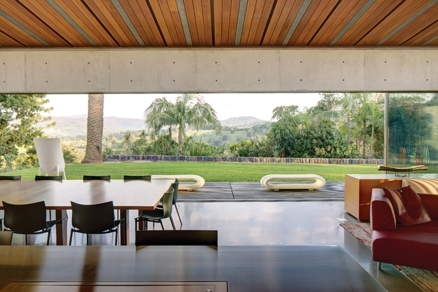 The public pavilion opens to a deck by the pool, framing long views to the mountains.