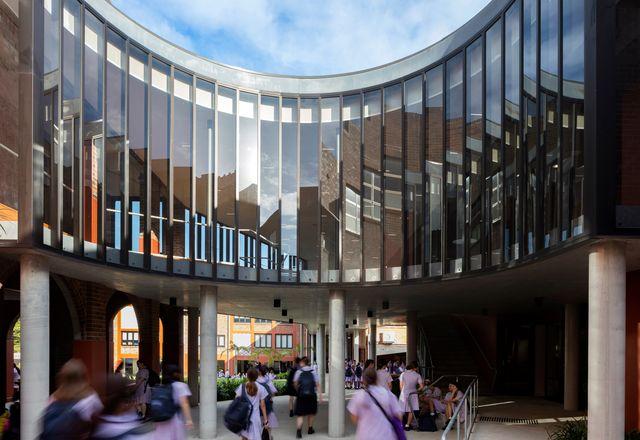 """在入口内部,一个新的""""脊柱""""吸引学生和游客穿过现有的建筑,并将一系列互不相连的空间连接起来。"""