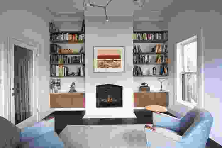 The second living room, at the front, original part of the house, features a fireplace and is lit with ample daylight. Artwork: Faye De Pasquale.