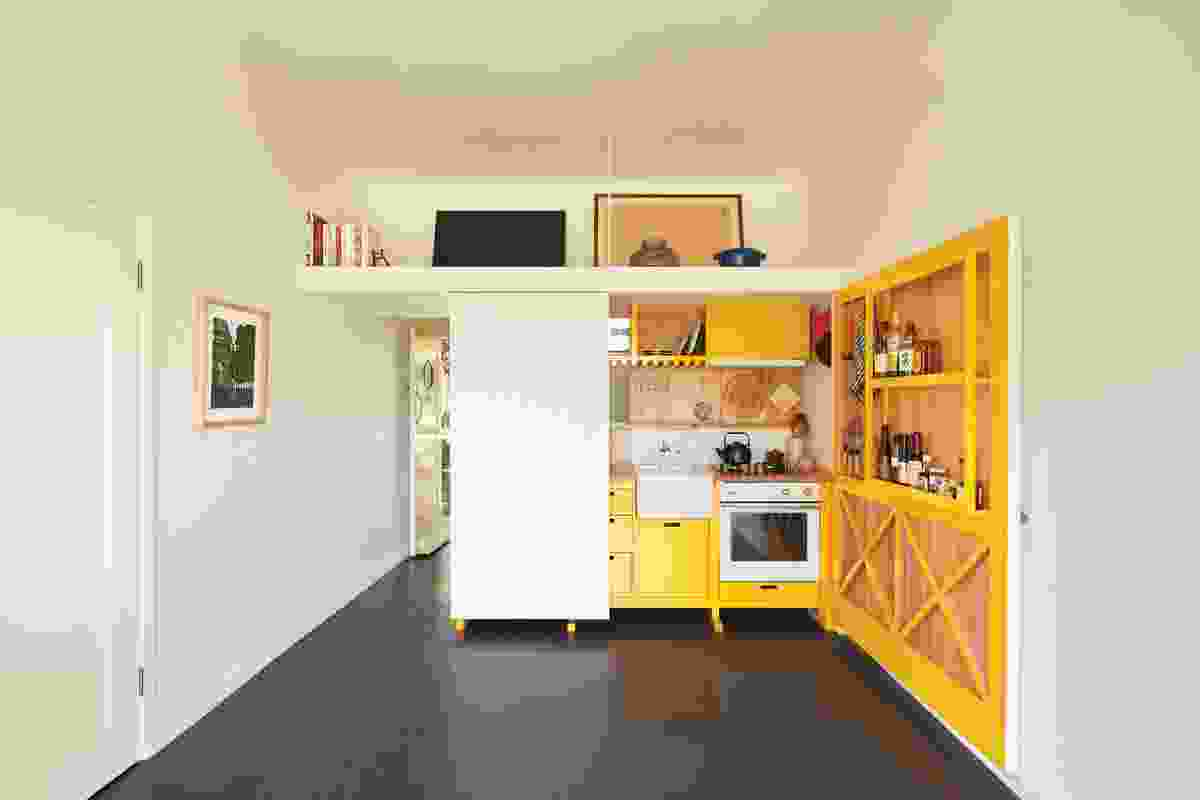 The splash of colour in the kitchen cabinetry was inspired by the bold yellow floor of Le Corbusier's Cabanon. Artwork (L-R): Sally Ross; Minnie Pwerle.