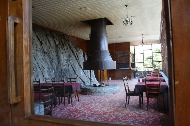 The hotel's formal dining room (lower level); its mighty rock wall references the mountains.