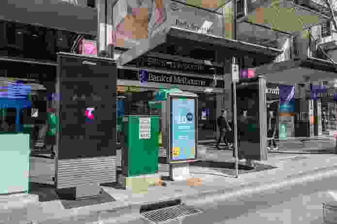 Two of the structures on the corner of Elizabeth and Bourke Streets, flanking an older model phone booth.