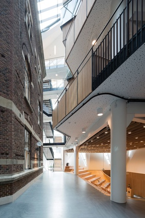 On the ground floor, a dark grey concrete floor leads past an open and inviting timber lecture hall.