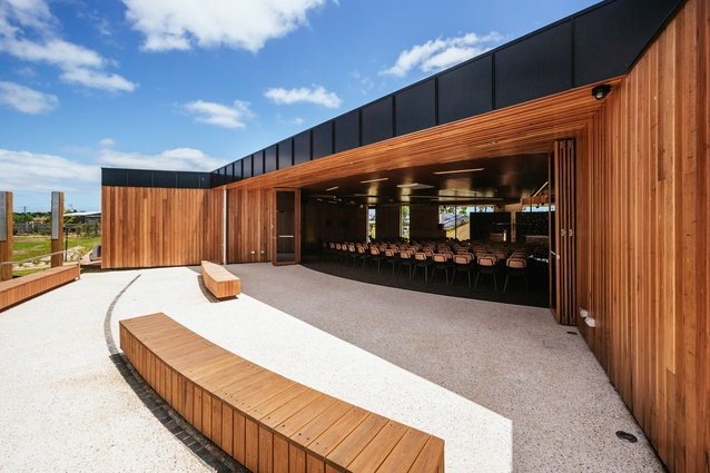 Bifold doors enable the interior space to extend out to the courtyard. Timber benches provide overflow seating, or serve as bleachers for games on the basketball courts opposite.