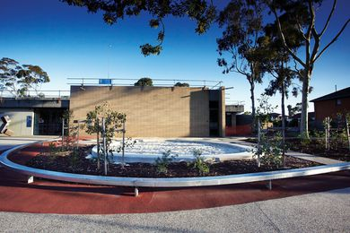 Young gum trees surround a circular sandpit in Preston Library's forecourt.
