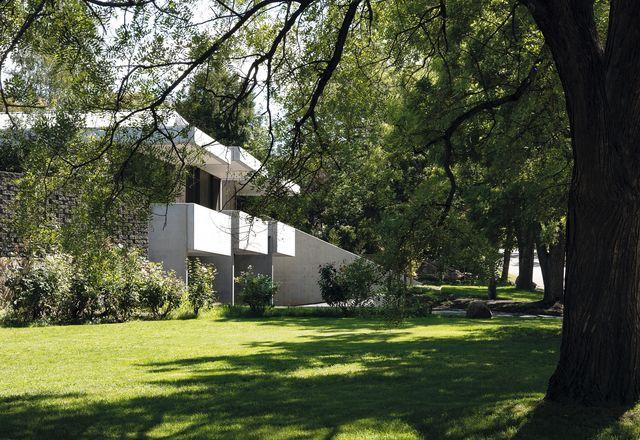 从街道上看,联排别墅呈现出一种坚固而优雅的混凝土形式,远离修剪整齐的草坪。