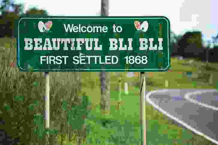 """The town sign for Bli Bli on Queensland's Sunshine Coast welcomes visitors to """"Beautiful Bli Bli, first settled 1868,"""" in a message ornamented with butterflies."""