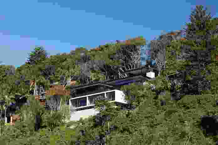 The house is perched precariously on a steep embankment.