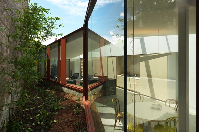 A faceted hallway ramps around a diminishing garden in the Annandale House by CO-AP Architects.
