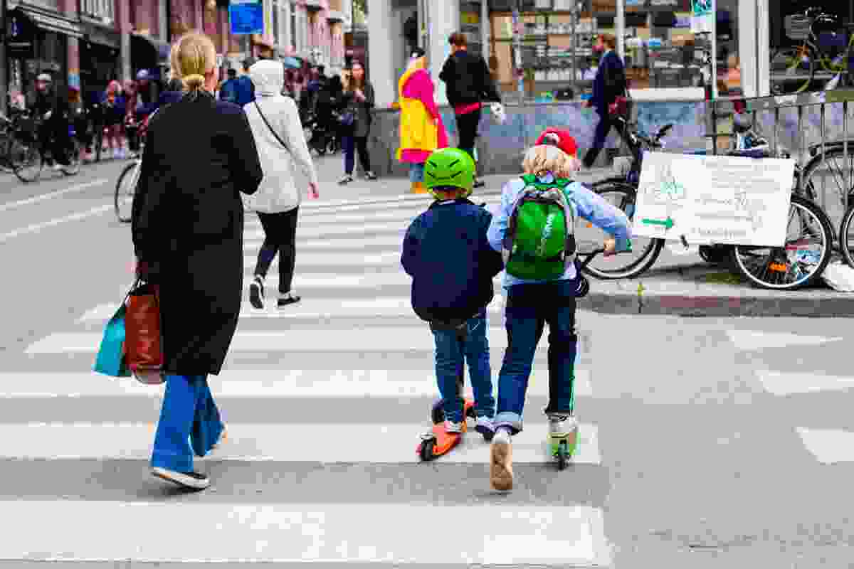 Children crossing a road on scooters, Stockholm, Sweden.