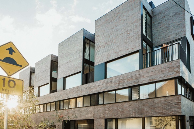 The four townhouses present a unified facade to the street.