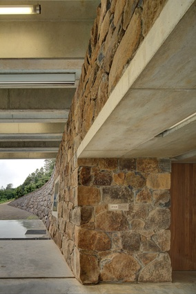 A stone wall, constructed from stones found on site, rises from the road and curves to form the rear wall.