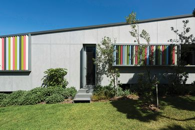 Vertical sun blades, in a fun palette of foliage-inspired colours, draw the garden into the fabric of the building.