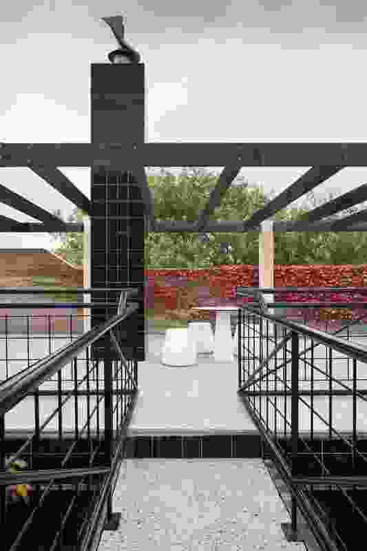 The pergola-framed roof terrace is accessed via a bridge at the top of the external stairs.