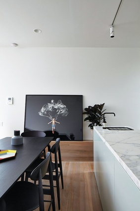 A neat, contemporary kitchen and dining space is slightly elevated from the first-floor living area. Artwork: Jeremy Blincoe.