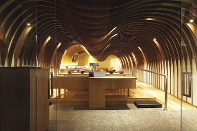 Curving plywood panels arc across the ceiling of Takada's Cave restaurant.