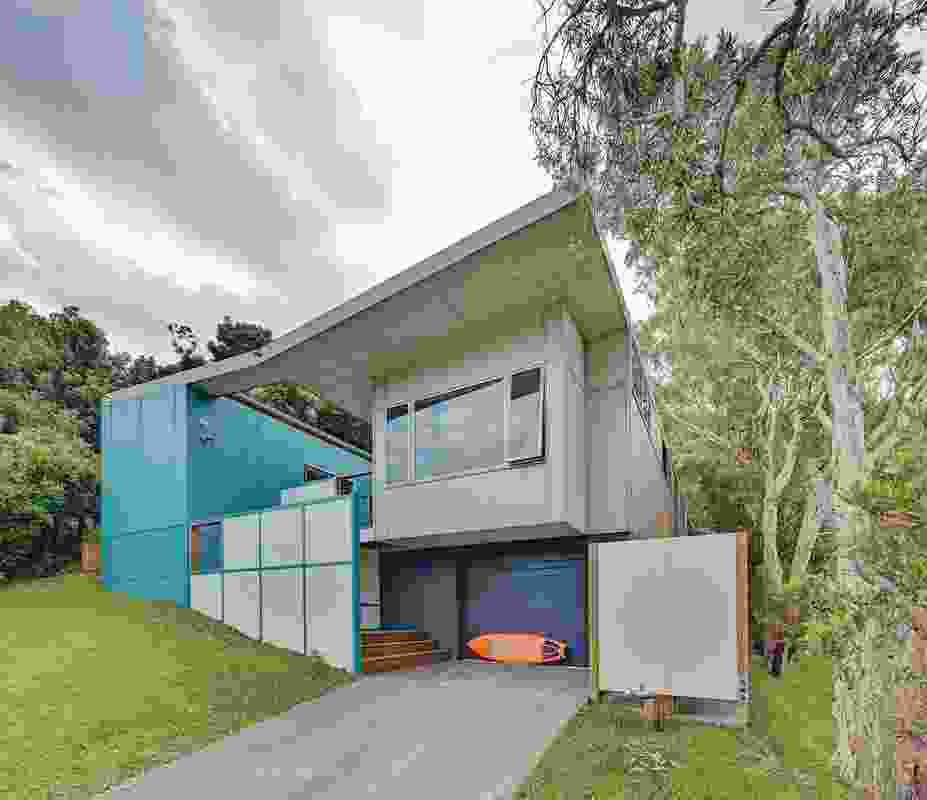 The house celebrates the robust material of fibre cement and uses high-level glazing and raked ceilings to engage with the landscape.