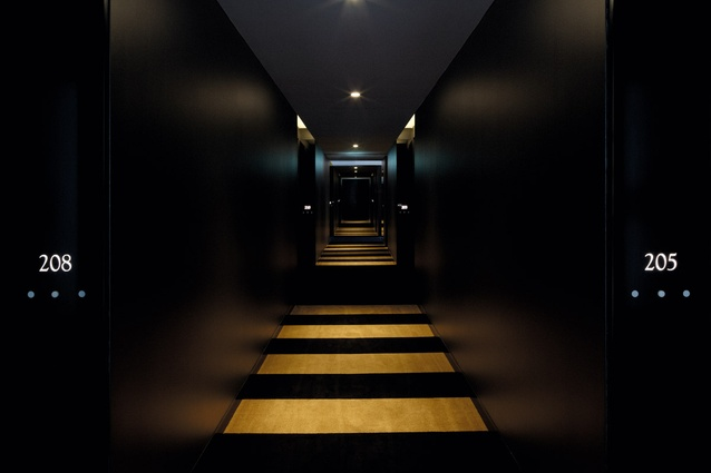 Striped carpet and recessed downlights lead along the corridor.
