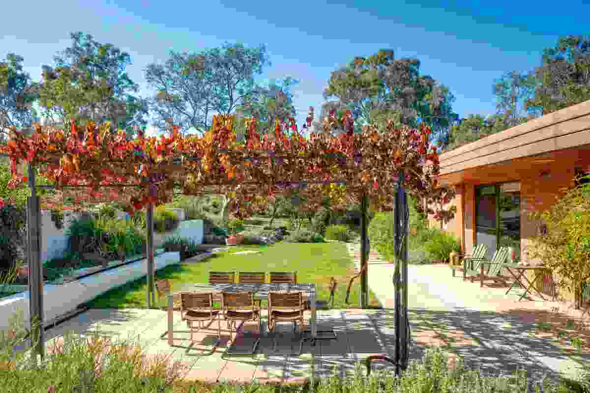 A parterre with fountain and arbour makes an outdoor dining area.
