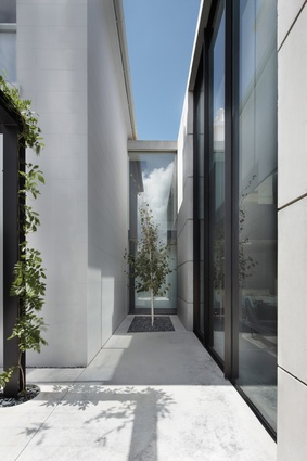 A large black-painted steel portal mediates the transition from the white plastered heritage villa to the raw concrete of the new pavilion.