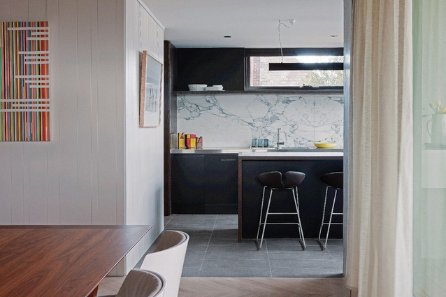 A generous kitchen features a solid timber island bench, stone splashback and grey porcelain floor tiles.