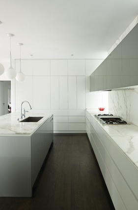 A neatly detailed kitchen continues the reserved and refined aesthetic.
